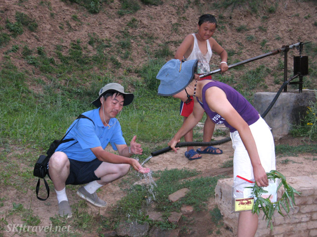Anrong washing his hands at the pump in Dang Jiashan Valley, Shaanxi Province, China.