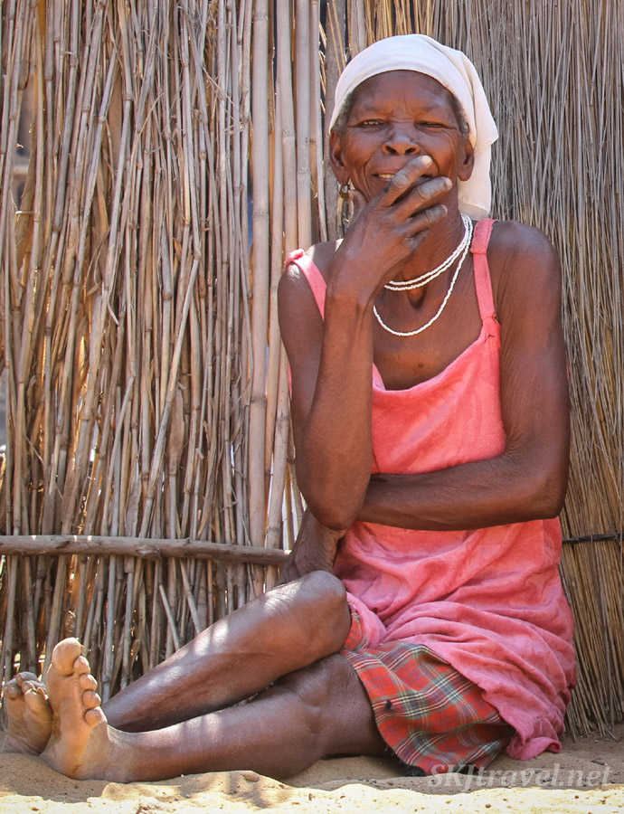 Granny Sabina's daughter sitting in her courtyard. Portrait. Divundu, Kavango region, Namibia.