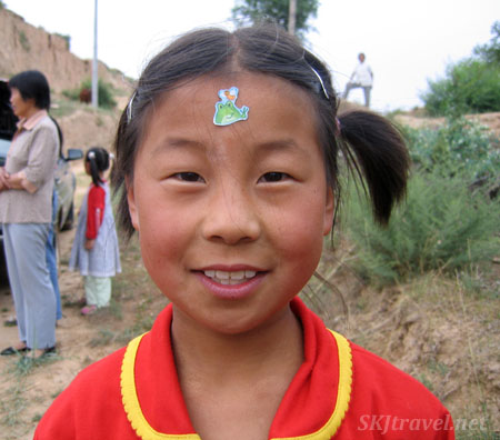 Chinese child with sticker on her forehead. Photo by Shara Johnson
