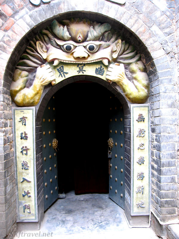 Open doorway beneath a monster's head with fangs. Photo by Shara Johnson