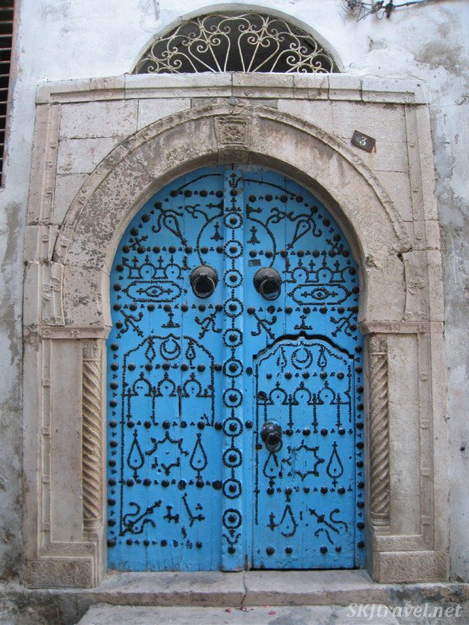 Bright blue door with metal black geometric designs. Typical of Tunisian medina, Tunis.