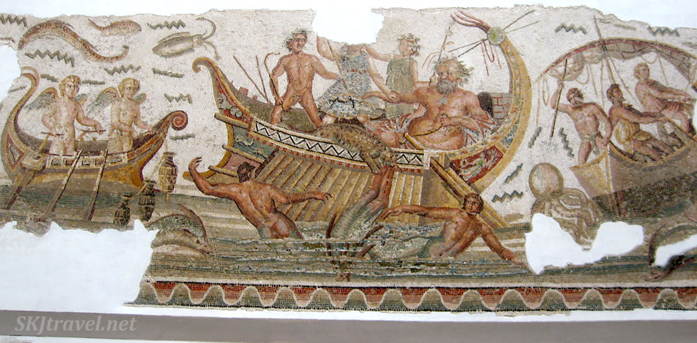 Scene of men, gods, angels and women in three ships at sea. A leopard jumps out of a ship. Octopus, eels, fish, crustaceans float in the water. Ancient Roman tile mosaic inside the Bardo Museum, Tunis, Tunisia.