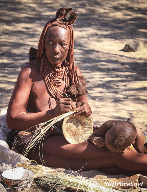 Eldest wife of the chief of a Himba clan, Kaokoland, Namibia, weaving a small basket with a toddler at her side.