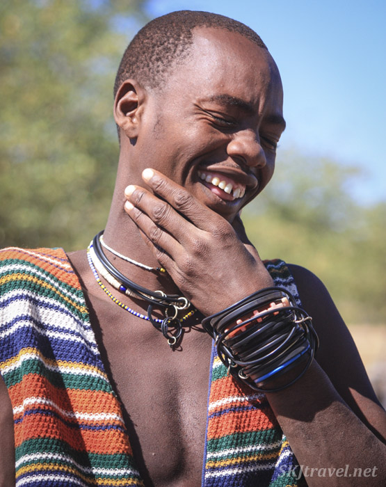 Laughing young Himba man inside his traditional kraal, Kaokoland, Namibia. Colorful clothing and jewelry.