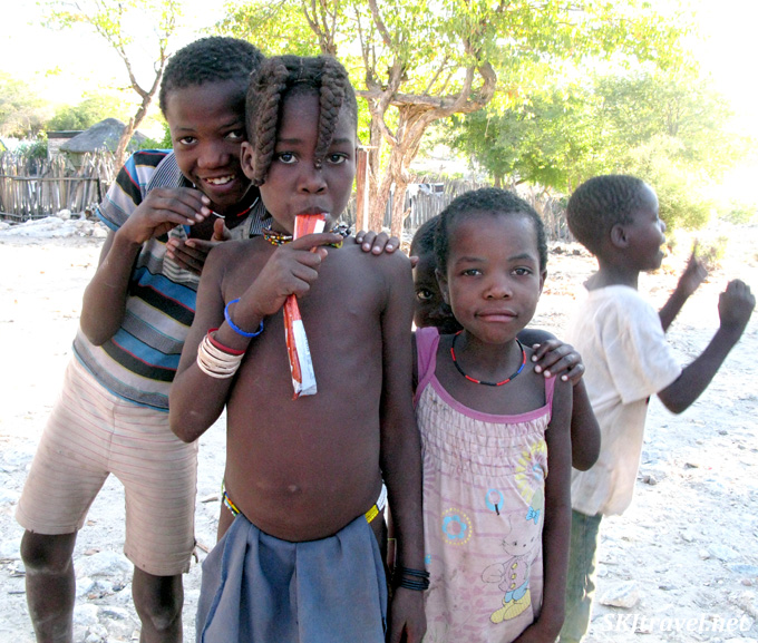 Children in both traditional and Western clothing playing together in a Himba village, Kaokoland, Namibia.