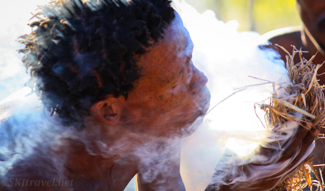 Smoke curling around a San man blowing into kindling lit with a spark, coaxing a flame with his breath at the Ju/'Hoansi-San Living Museum near Grashoek, Namibia.