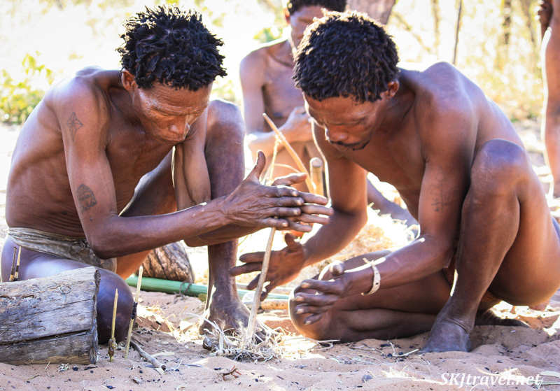 San men starting a fire by hand, rubbing a stick in dry kindling, at the Ju/'Hoansi-San Living Museum near Grashoek, Namibia.