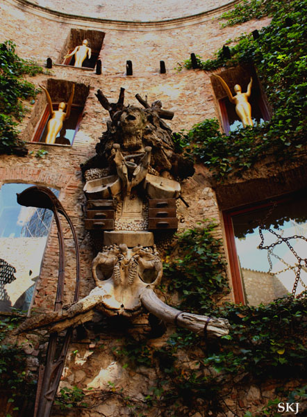 Outdoor courtyard with statues in window niches and ivy on the walls at Dali museum in Figueres Spain. photo by Shara Johnson