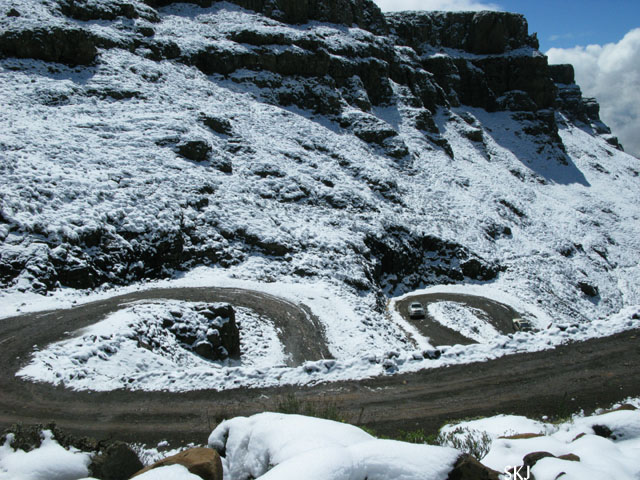 Two hairpins in a road with snow-covered roadside. Lesotho