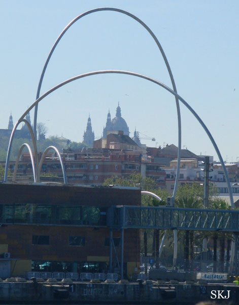 Looking toward the city from an ocean boardwalk through a large metal arch.