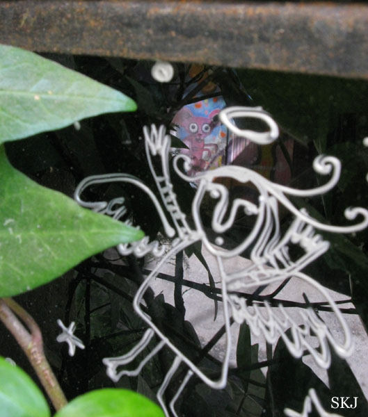 Window with white angel painted on it and reflection of pink cartoon character. photo by Shara Johnson