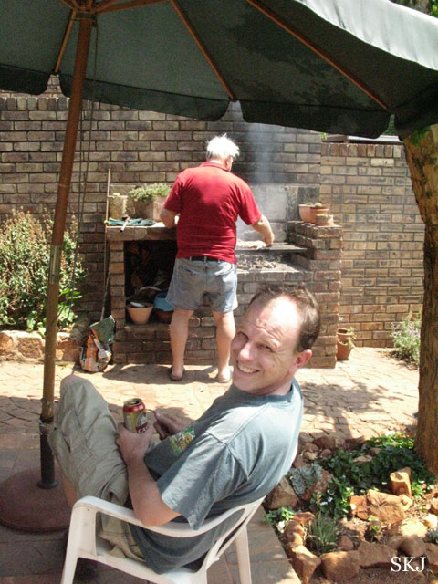 man holding beer and another one cooking at a grill
