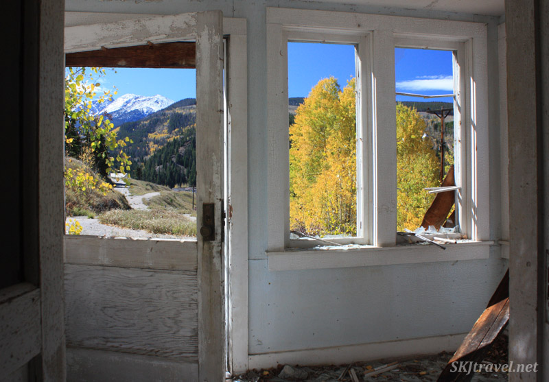 Looking out the front door and windows of an abandoned house in Gilman, Colorado.
