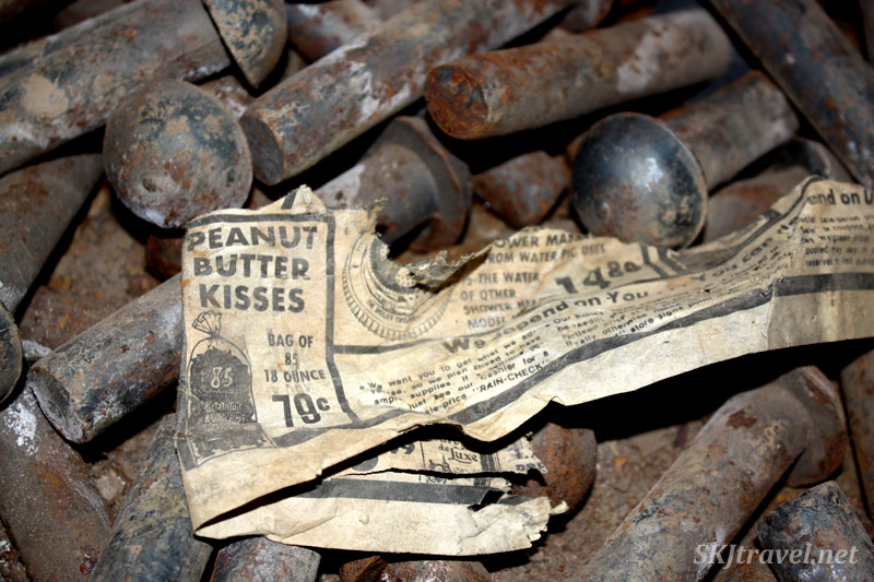 Newspaper clipping with an ad for 79-cent bag of peanut butter kisses, lying among industrial bolts in abandoned building, Gilman, Colorado.