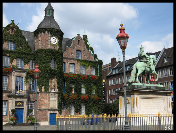 Courtyard in Dusseldorf, Germany, with a bronze statue of a horse and rider and stone buildings covered in ivy. Photo by Shara Johnson