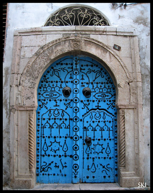 Bright blue door with ornate black geometric design on it in a concrete building in Tunis, Tunisia. Photo by Shara Johnson