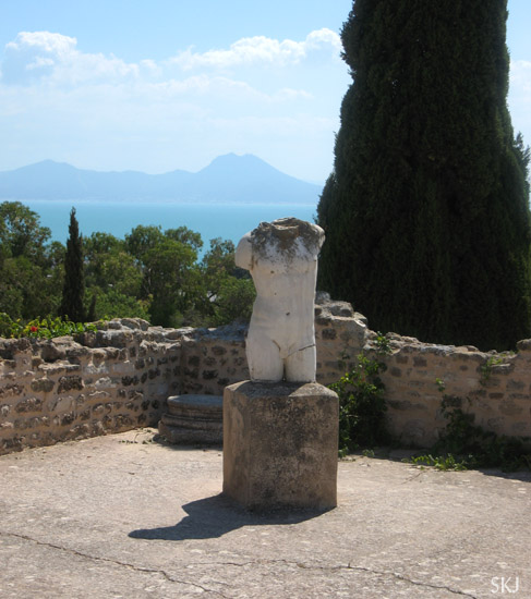 The torso of an ancient statue stand in a courtyard of a villa in the Roman ruins of Carthage in Tunis, Tunisia, the Mediterranean Sea in the background. Photo by Shara Johnson