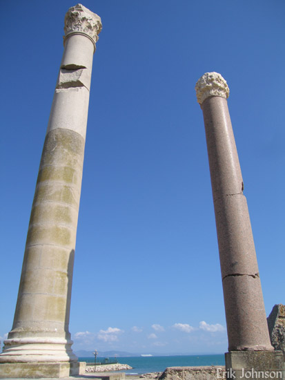 Tall pillars reach into a blue sky at the edge of the Mediterranean, the ruins of the bath complex at Carthage in Tunis, Tunisia. Photo by Shara Johnson