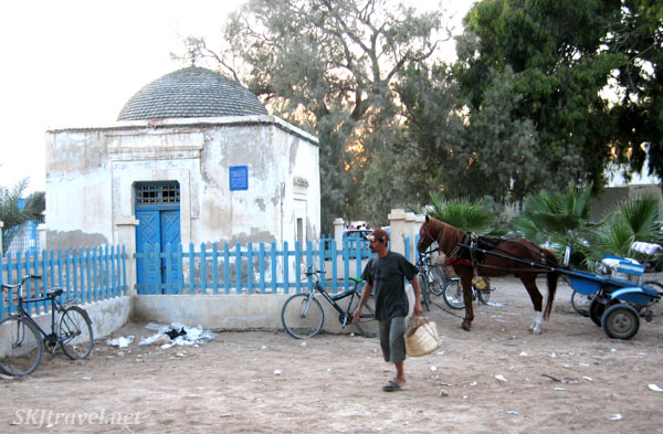 Man walking in front of white and blue building with horse in the background in Djerba Tunisia. photo by Shara Johnson
