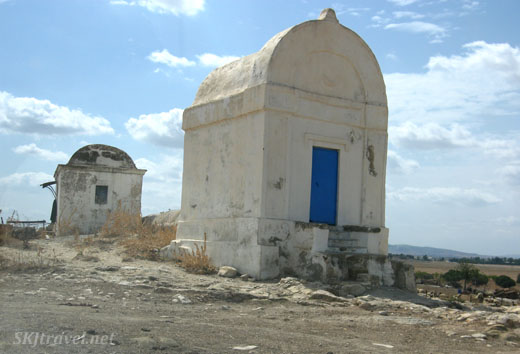 Little white buildings with typical bright blue door along the roadside in Tunisia.