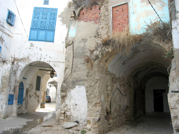 Two archways, one abandoned and crumbling next to a white one with lantern hanging down and blue windows in Tunis Tunisia. photo by Shara Johnson