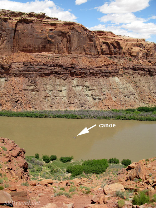 Looking down from a saddle in the high canyon walls onto a canoe in Green River, Utah.