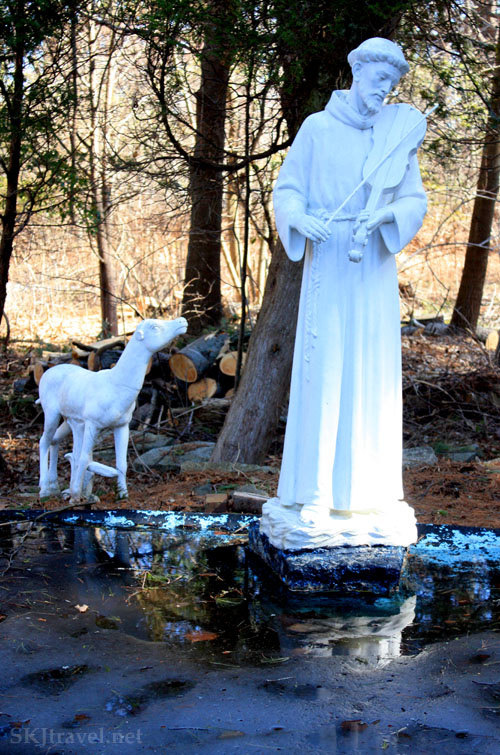 Statue of a man playing a violin and a sheep beside a half-frozen pool at a Lithuanian monastery, Maine. Photo by Shara Johnson