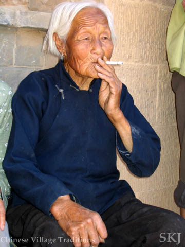 Old woman with bound feet in blue pantsuite smoking a cigarette in a peasant village in China. Photo by Shara Johnson