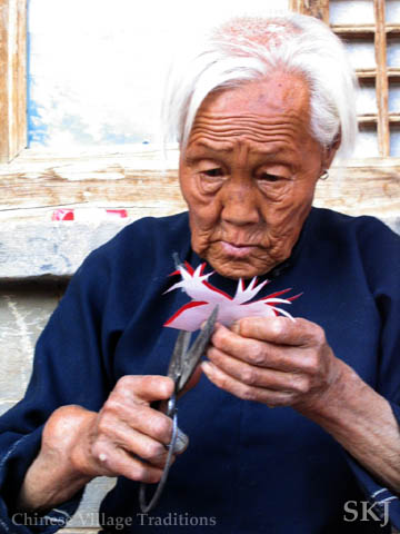 Elderly woman in Shaanxi Province, China, cutting red paper into two birds. Photo by Shara Johnson