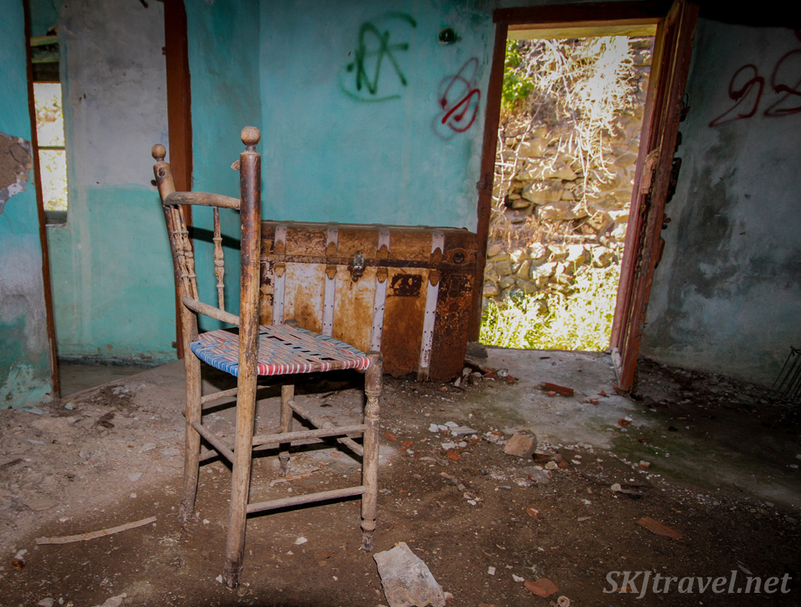 Old wicker seat chair inside an abandoned home in Volissos, Chios Island, Greece. Positioned to be facing an open door with bright light outside, and chest from the past.